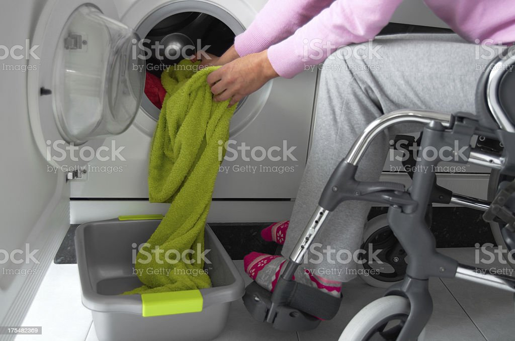 Disabled woman in a wheelchair doing laundry. stock photo