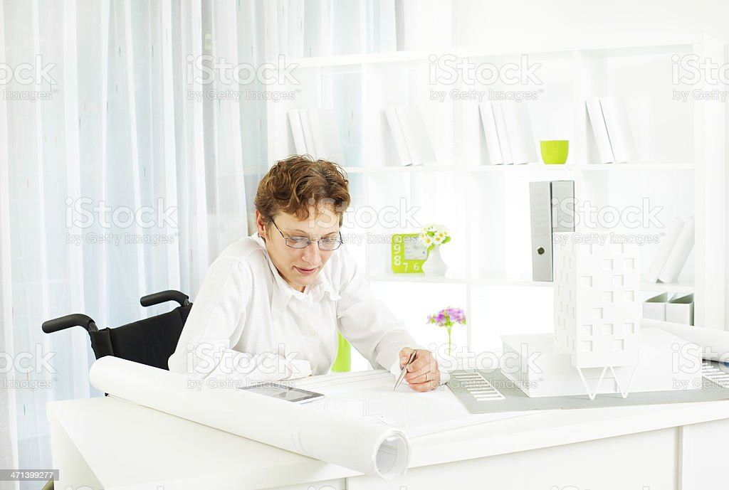 Disabled Woman in wheelchair at work. stock photo