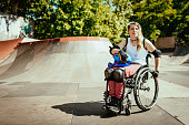 istock Disabled woman in wheelchair doing stunts in skate park 1257806762