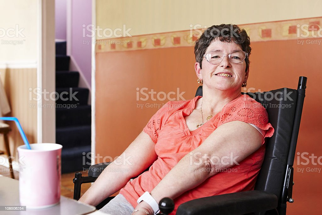 disabled woman in wheelchair enjoying hot drink at home stock photo
