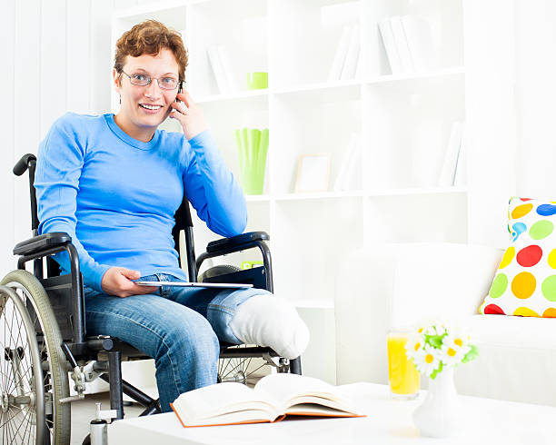 Disabled Woman in wheelchair talking on the phone. stock photo
