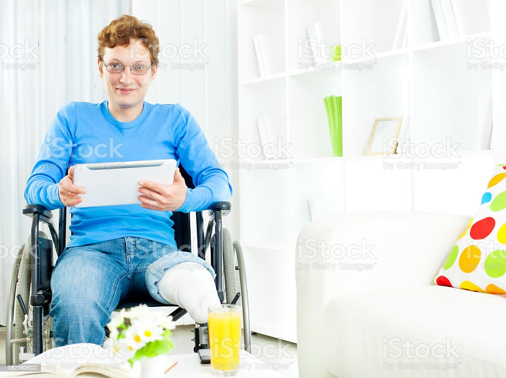 Disabled Woman in wheelchair using Digital Tablet at home. stock photo