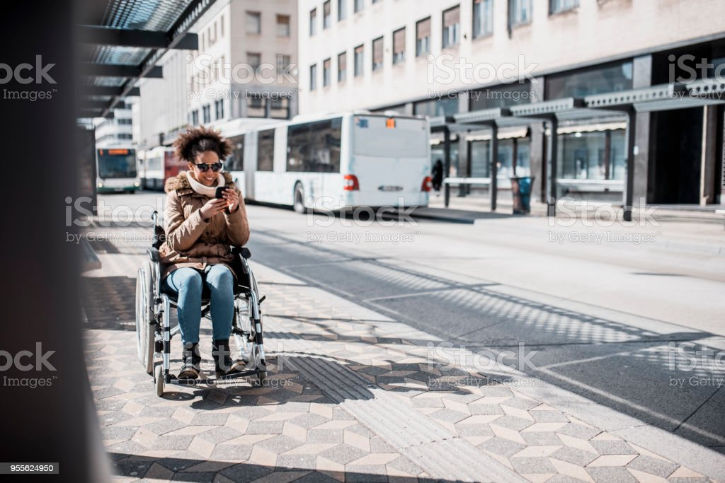 Behinderte Frau im Rollstuhl mit Smartphone und warten auf einen bus – Foto
