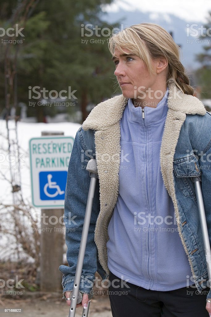 Disabled woman on crutches stock photo