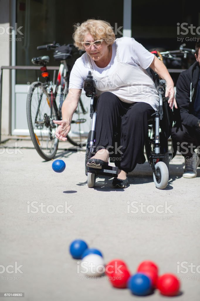 Disabled woman on wheelchair playing boccia on asphalt court. stock photo