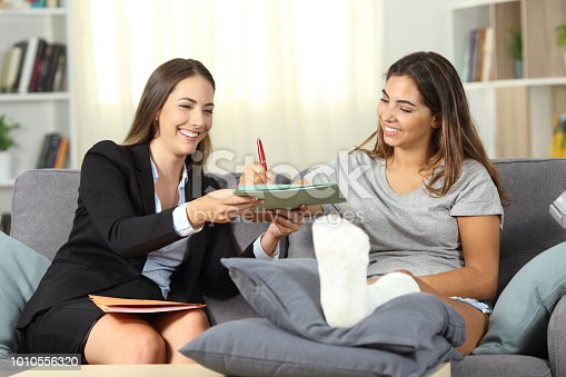 istock Disabled woman signing a contract with a insurance agent 1010556320