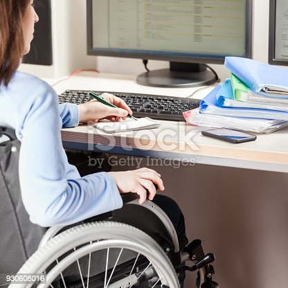 1144373653 istock photo Disabled woman sitting wheelchair working office desk computer 930608016