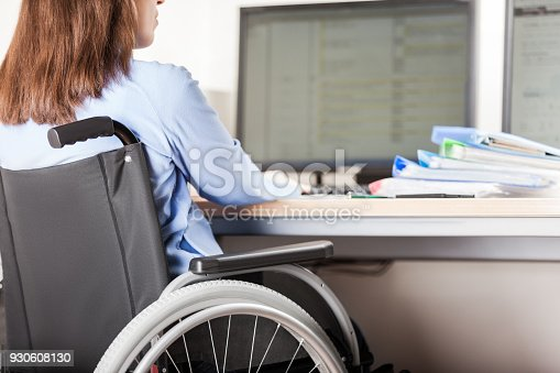 1144373653 istock photo Disabled woman sitting wheelchair working office desk computer 930608130