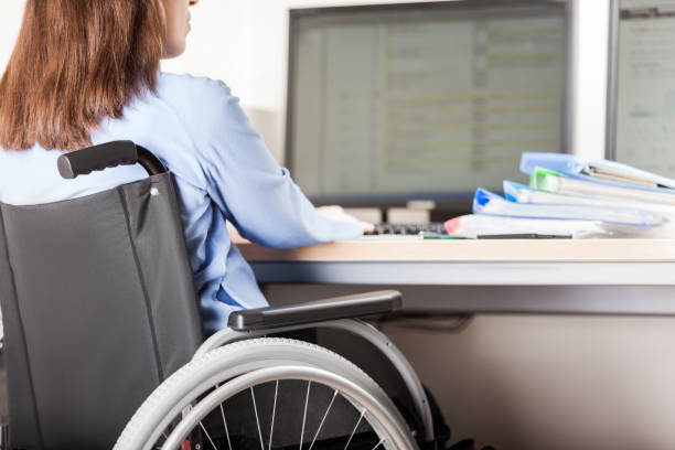 Disabled woman sitting wheelchair working office desk computer Disabled young business woman person sitting wheelchair working office desk computer persons with disabilities stock pictures, royalty-free photos & images