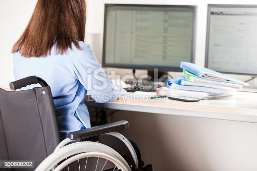 1144373653 istock photo Disabled woman sitting wheelchair working office desk computer 930608202