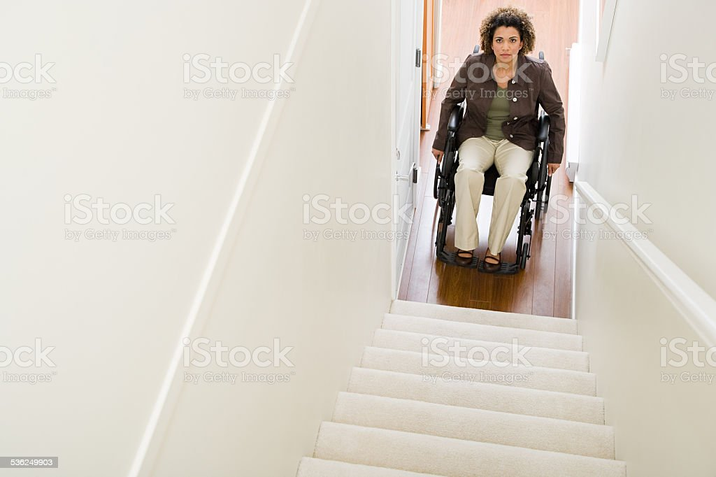 Disabled woman trapped at bottom of stairs stock photo
