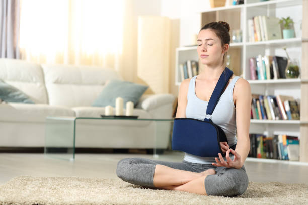 Disabled woman with a sling practicing yoga exercise stock photo