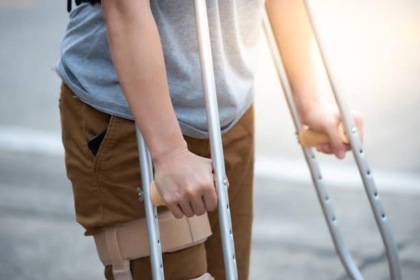 後ろ側に立って松葉杖や歩行スティックや膝のサポートを持つ障害者の女性, 半分ボディ. - 杖 ストックフォトと画像