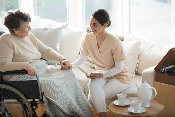 Disabled woman with medical assistant A disabled old woman on a wheelchair holding hand of a tender professional medical assistant during tea time in a living room of luxury retirement home military private stock pictures, royalty-free photos & images