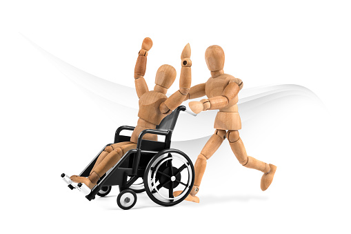 941792734 istock photo disabled wooden mannequin in wheelchair is happy with friend - winnig? having fun? 1218599895