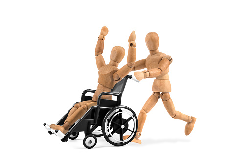 941792734 istock photo disabled wooden mannequin in wheelchair is happy with friend - winnig? having fun? 941792928