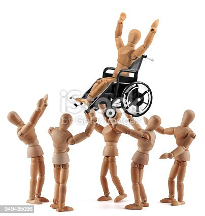 941792734istockphoto disabled wooden mannequin in wheelchair picked up by friends - jubilation 949435096