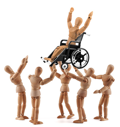 941792734 istock photo disabled wooden mannequin in wheelchair picked up by friends - jubilation 949435096