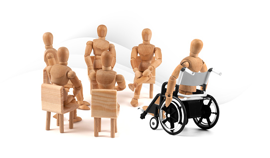 941792734 istock photo disabled Wooden Mannequin in wheelchair talking to a group of people 1218599990