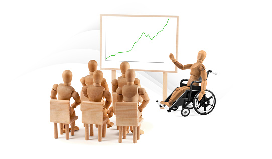 941792734 istock photo disabled Wooden Mannequin in wheelchair talking to a group of people 1218600522