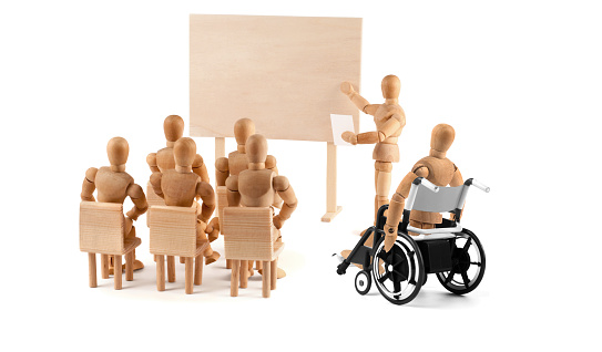 941792734 istock photo disabled Wooden Mannequin in wheelchair talking to a group of people 939985578