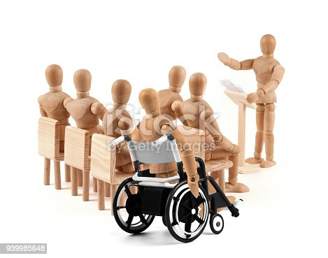 941792734istockphoto disabled Wooden Mannequin in wheelchair talking to a group of people 939985648