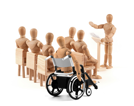 941792734 istock photo disabled Wooden Mannequin in wheelchair talking to a group of people 939985648