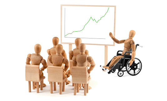 941792734 istock photo disabled Wooden Mannequin in wheelchair talking to a group of people 939985764