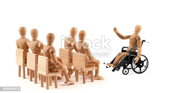941792734istockphoto disabled Wooden Mannequin in wheelchair talking to a group of people 939985828