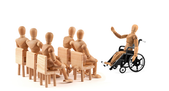 941792734 istock photo disabled Wooden Mannequin in wheelchair talking to a group of people 939985828