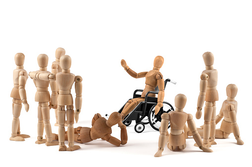 941792734 istock photo disabled Wooden Mannequin in wheelchair talking to a group of people 939986352