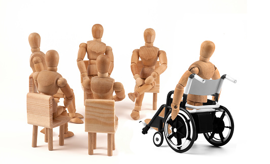 941792734 istock photo disabled Wooden Mannequin in wheelchair talking to group therapy 939986316