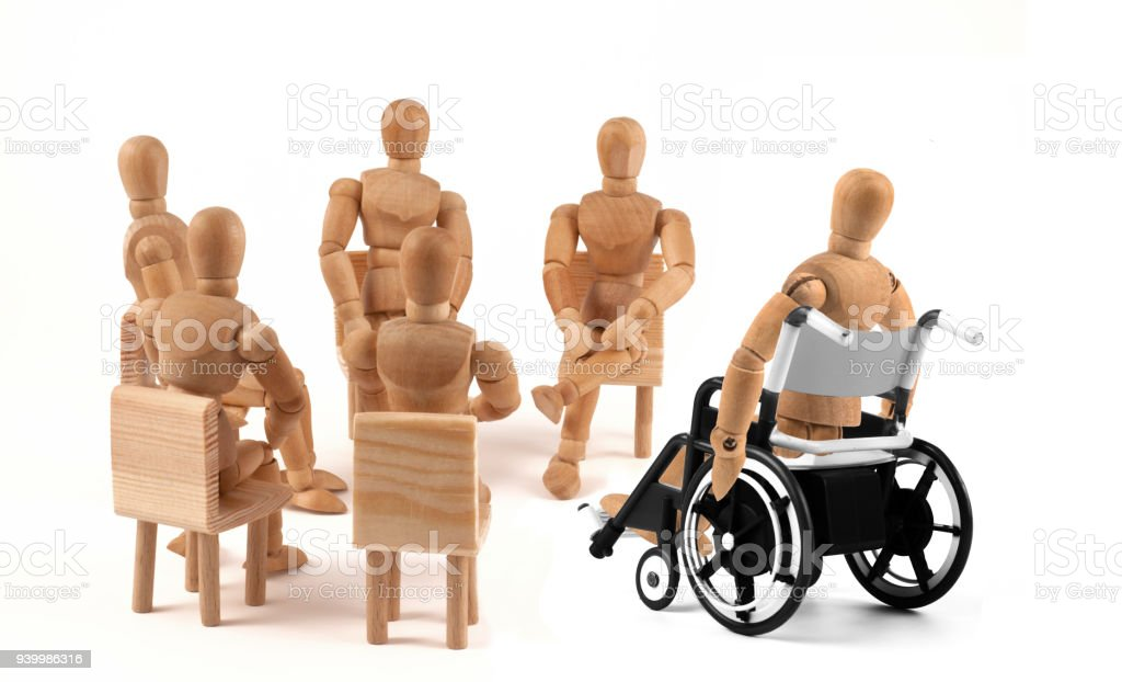 disabled Wooden Mannequin in wheelchair talking to group therapy stock photo