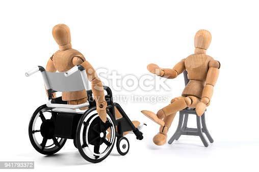 941792734istockphoto disabled wooden mannequin in wheelchair talking with somebody. Talkshow? Therapist? 941793372
