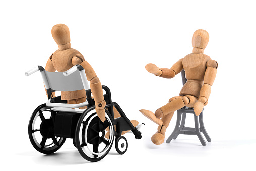 941792734 istock photo disabled wooden mannequin in wheelchair talking with somebody. Talkshow? Therapist? 941793372