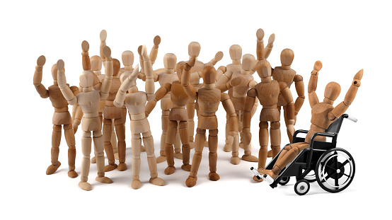 941792734 istock photo disabled wooden mannequin in wheelchair together with friends in a crowd 937410960