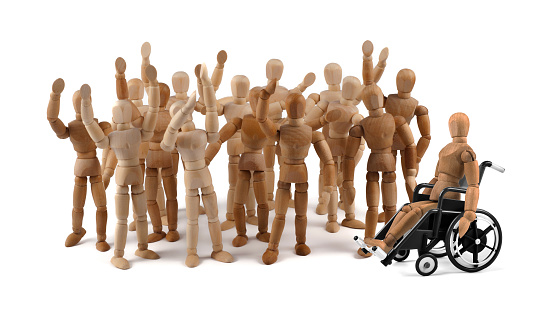 941792734 istock photo disabled wooden mannequin in wheelchair together with friends in a crowd 949433014