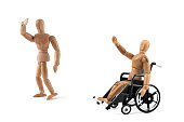 disabled wooden mannequin in wheelchair waving a friend - good bye