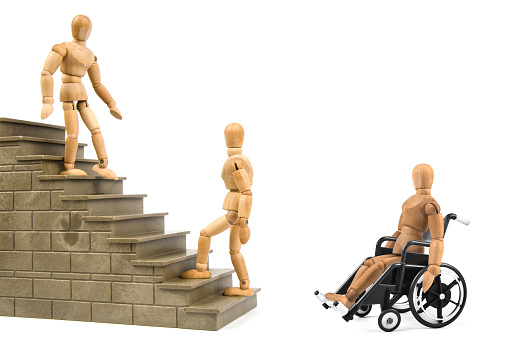 941792734 istock photo disabled wooden mannequin in wheelchair with barrier problems 936885944