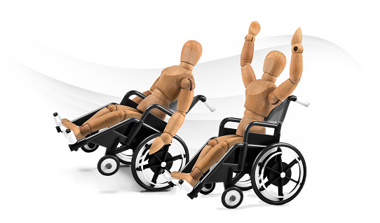 941792734 istock photo disabled wooden mannequins in wheelchair are happy - winnig? having fun? 1218600625
