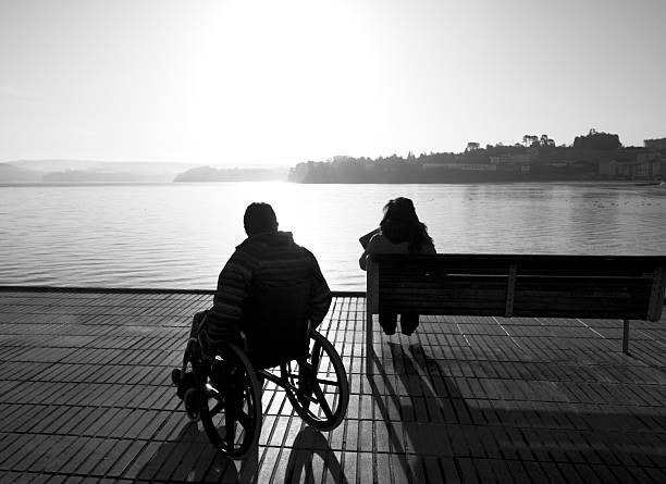 Disabled young adult in wheelchair by the sea. stock photo