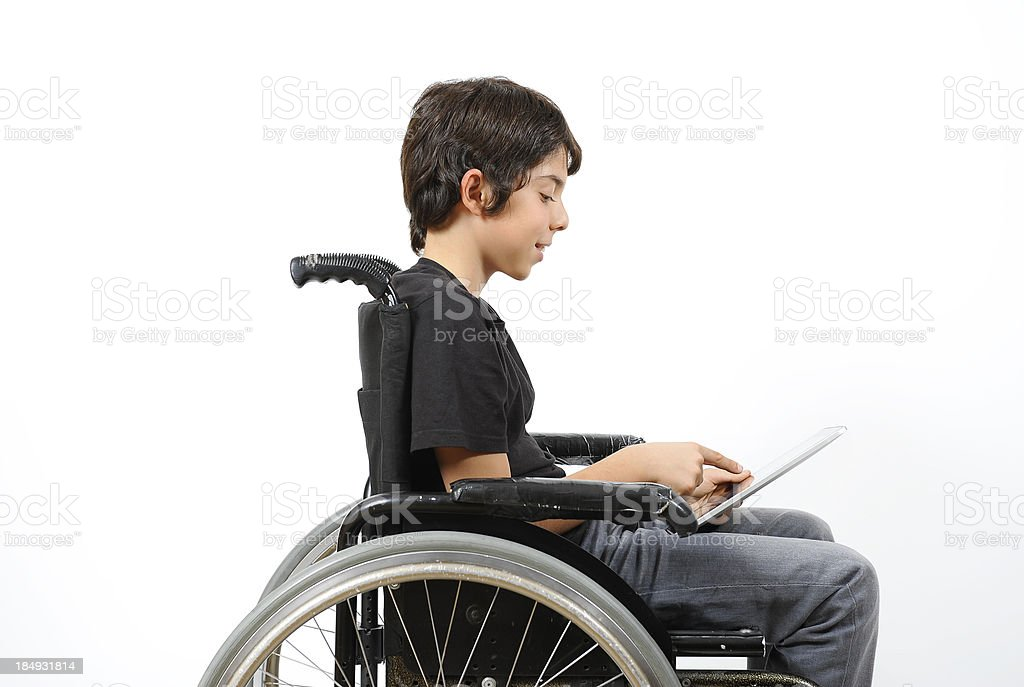 Disabled young boy looking at digital tablet stock photo