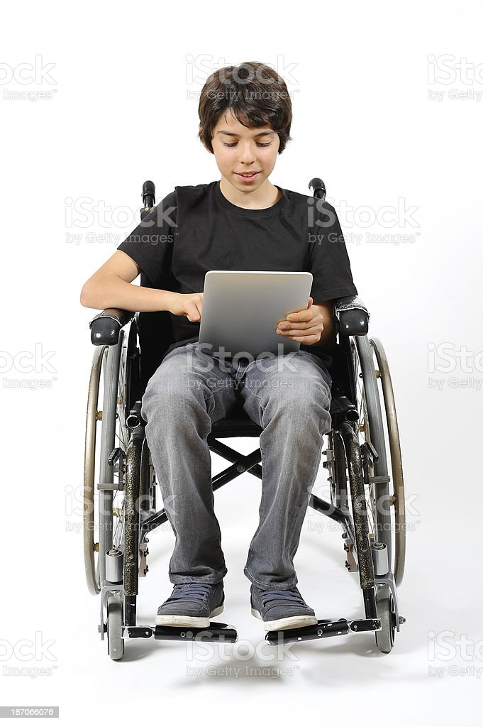 Disabled young boy looking at digital tablet royalty-free stock photo