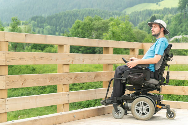 disabled Young man in electric wheelchair on a boardwalk enjoying his freedom and observing nature stock photo