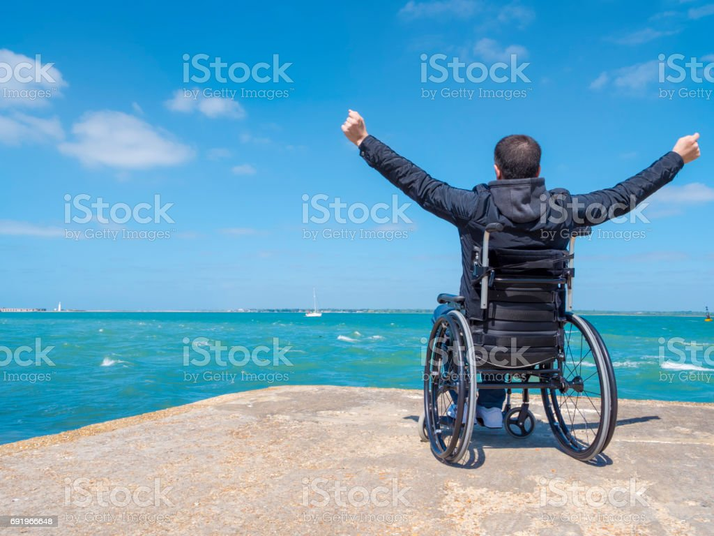 Disabled young man sitting in a wheelchair stock photo