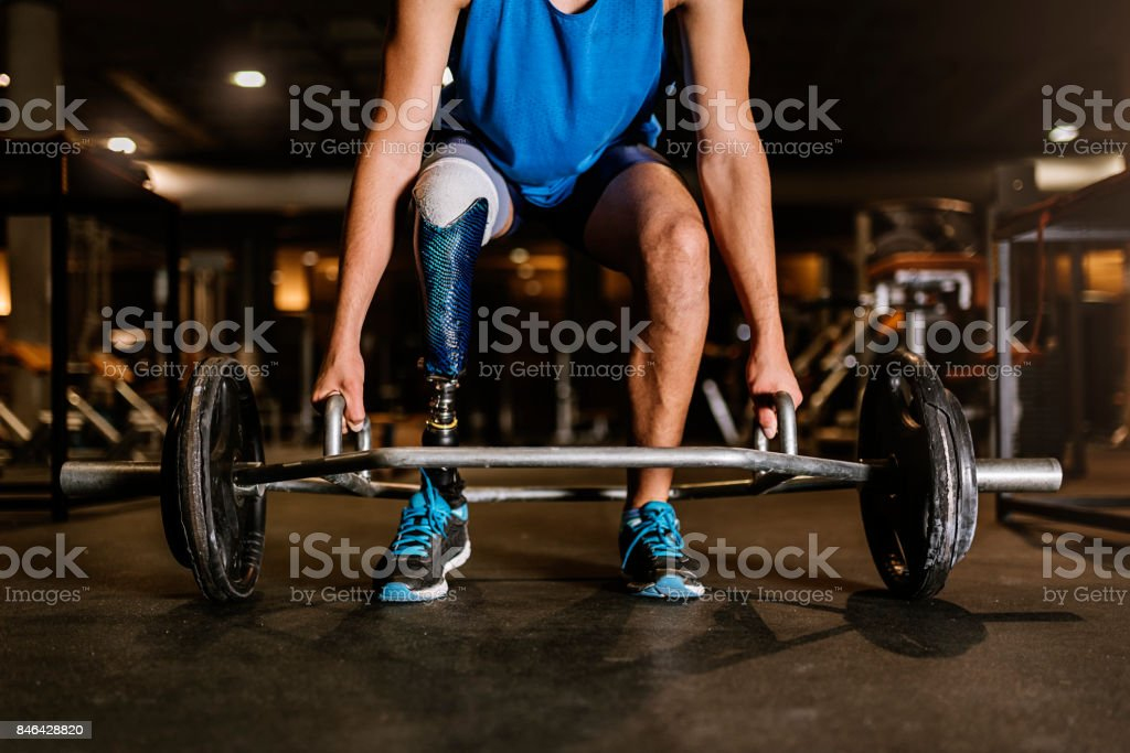 Disabled young man training in the gym. stock photo