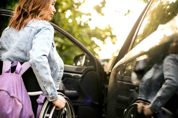 Disabled young woman getting in a car stock photo