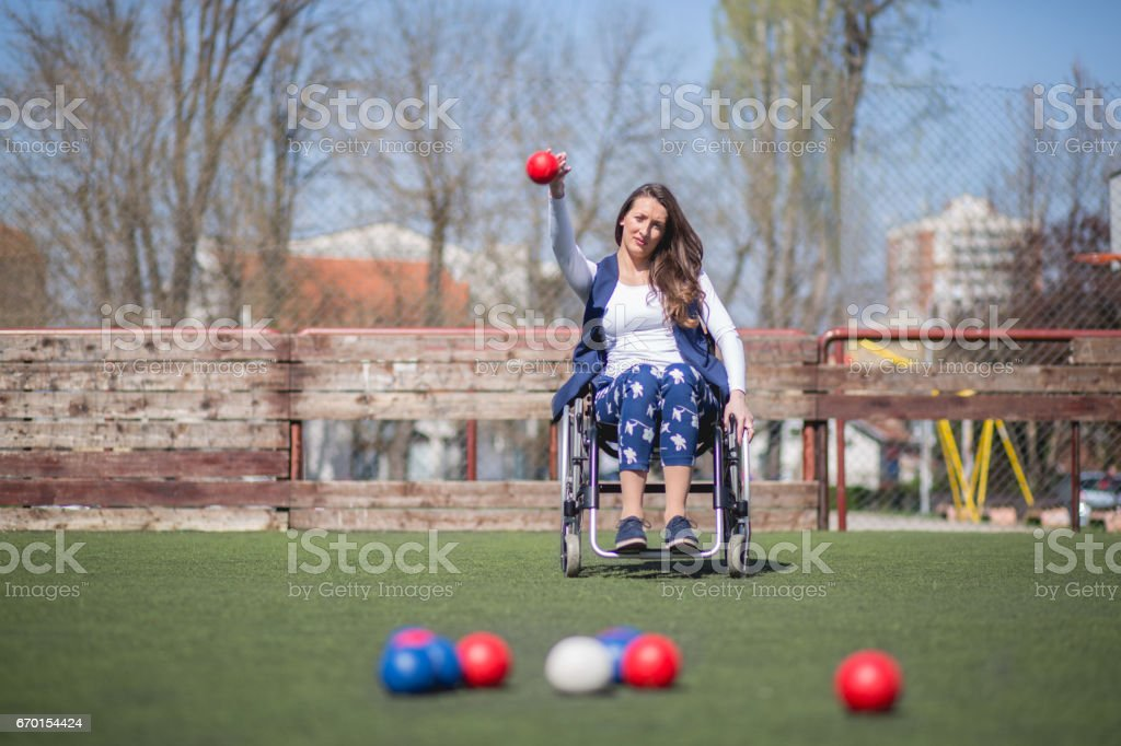Disabled young woman on wheelchair playing boccia on asphalt court. stock photo