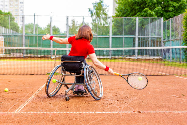 femme jeune handicapée sur fauteuil roulant, jouer au tennis sur un court de tennis. - sports en fauteuil roulant photos et images de collection