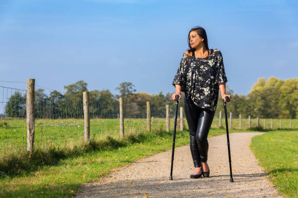 Disabled young woman walks on crutches on rural footpath stock photo